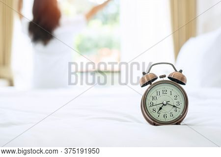 Closeup Alarm Clock With Background Of Happy Woman Stretching In Bed After Waking Up, Young Adult Fe