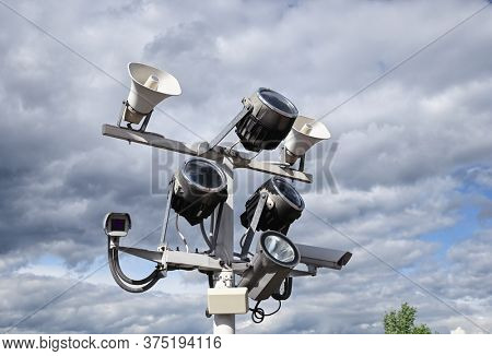 Close up of outdoor surveillance cameras, floodlights and loudspeakers on street pole