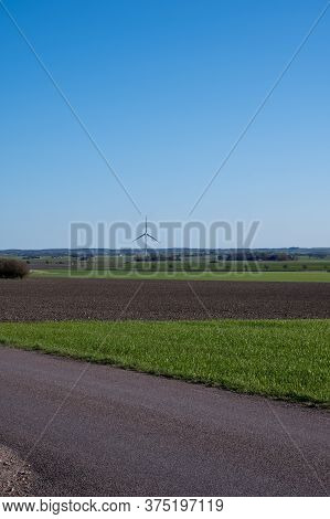 A Single Wind Turbine Stands Tall In The Flat Farmlands Of Skåne (scania) In Southern Sweden