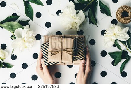 Flat lay arrangement female's hands holding gift boxes among presents and flowers, top view on white polka dots background.