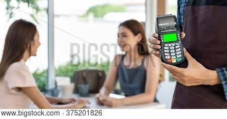 Panoramic close up of waiter hand hold credit card reader for contactless payment with customers in restaurant background. New normal restaurant contactless payment concept.