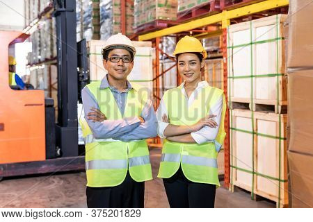 Portrait of Asian warehouse manager and worker arm crossed with warehouse worker operate forklift to check inventory in background. Reopening business warehouse technology and logistic concept.