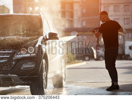 Silhouette Of A Strong Man Holding A Hose And Washing His Black Car With A Water Jet, Water Drops An