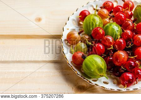 Ripe Gooseberry In Ceramic Plate, Place For Text, Top View, Summer Harvest Of Berries.red And Green
