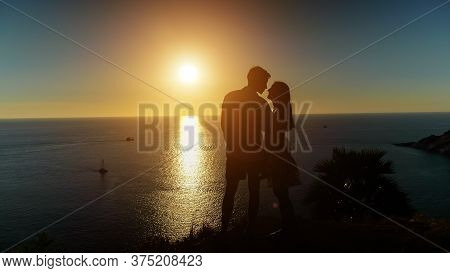 Couple Silhouettes Stand On Beach Edge And Kiss Admiring Pictorial Sunset Reflecting In Calm Ocean W