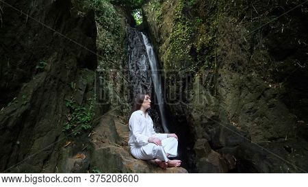 Concentrated Woman With Loose Dark Hair In White Costume Meditates Sitting In Yoga Lotus Position On