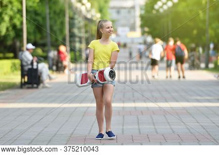 Smiling Girl Child Carries Her Discharged Hoverboard In A Public Park In The Background Of People