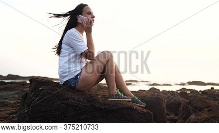 Relaxed Woman Sitting On Stone And Speaking On Smartphone On Shore. Side View Of Pleasant Woman Spen