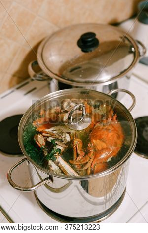 Red Boiled Crabs In A Saucepan. Blue Crabs Are Cooked In A Saucepan With A Glass Lid.