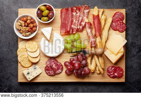 Cheese, meat, grapes and olives antipasto. Appetizer selection board. Top view. Flat lay