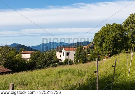 Large green lawn and at the bottom a small new village house. Beautiful Swiss architecture