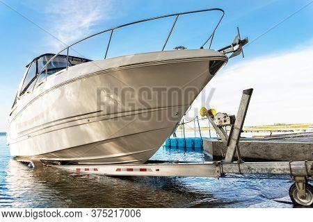 Big Luxury Cabin Motorboat Cruiser Yacht Launching At Trailer Ramp On River Or Lake. Warm Morning Su