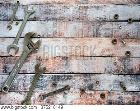 Wrenches And Fasteners Are Located Around The Wooden Background. Empty Space For Text. Background Wi