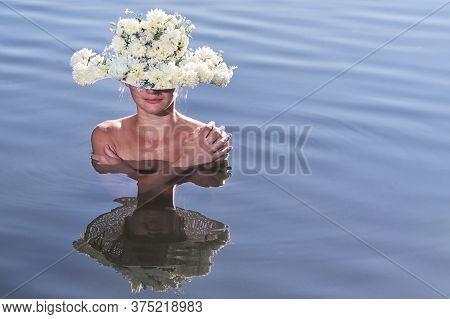 Portrait Of Young Woman With Flowers Hat In Lake