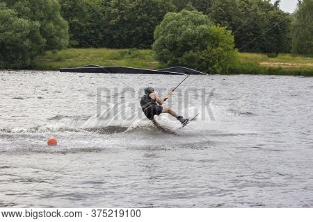 Wakeboarder On Wakeboard Landed In Water Surrounded By Spray. A Man Rides Water Skis At High Speed.
