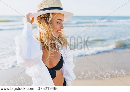 Portrait Of Slim Smiling Young Woman In A Black Swimsuit And White Shirt Standing At The Beach With