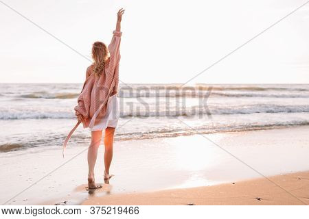A Young Slender Girl Stands Alone On The Beach Or Ocean And Look At The Horizont. A Woman Dressed In