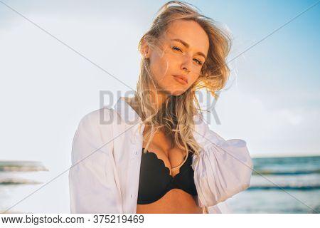 Beautiful Blonde Slim Girl In A Black Bikini And White Shirt On The Beach The Ocean Against The Sun.
