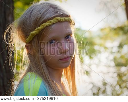 Portrait Of A Blonde Girl With Blue Eyes At Sunset In The Backlight