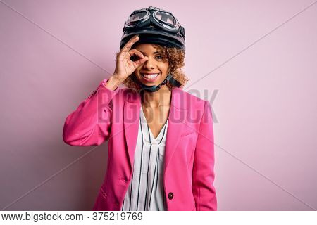 African american motorcyclist woman with curly hair wearing moto helmet over pink background doing ok gesture with hand smiling, eye looking through fingers with happy face.