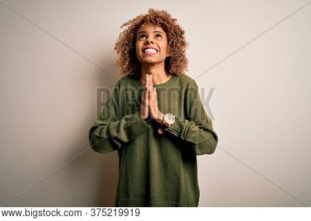 Beautiful african american woman with curly hair wearing casual sweater over white background begging and praying with hands together with hope expression on face very emotional and worried. Begging.