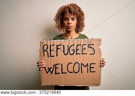 African american woman asking for immigration holding banner with wlecome refugees message with a confident expression on smart face thinking serious