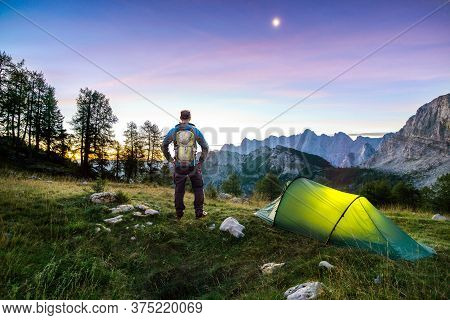 Hiker With Backpack Standing On Mountain And Tent Glowing Under A Moon Night Sky At Sunset Or Sunris