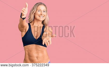 Middle age fit blonde woman wearing bikini looking at the camera smiling with open arms for hug. cheerful expression embracing happiness.