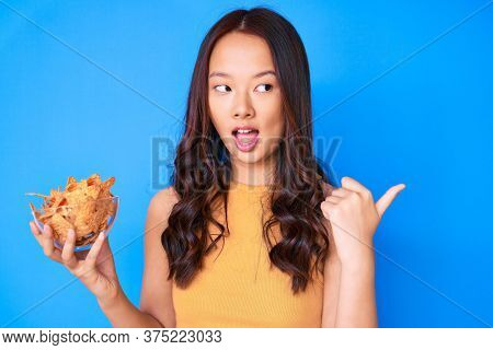 Young beautiful chinese girl holding nachos potato chips pointing thumb up to the side smiling happy with open mouth