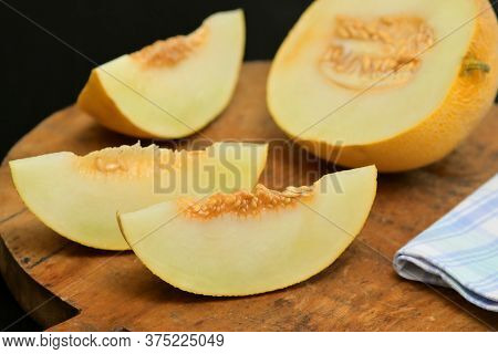 Yellow Melon With Slices On A Wooden Table