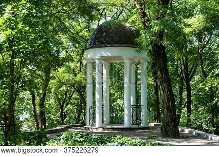 Summer Landscape, Sunny Morning In The Old Park With A Summer Arbor Of White Color With Columns. Man