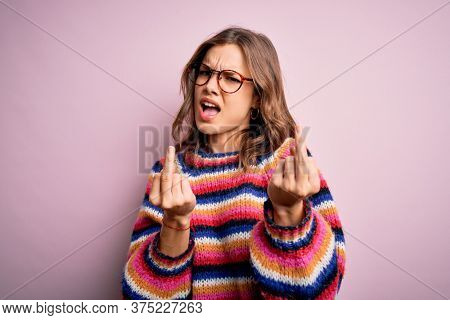 Young beautiful blonde girl wearing glasses and casual sweater over pink isolated background Showing middle finger doing fuck you bad expression, provocation and rude attitude. Screaming excited