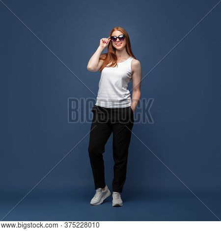 Confident In Eyewear. Young Woman In Casual Wear On Blue Studio Background. Bodypositive Character,