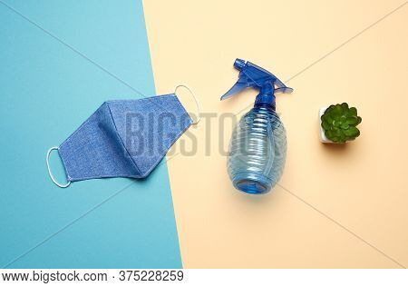 Reusable Textile Mask, Blue Bottle For Disinfector On A Beige-blue Background, Top View