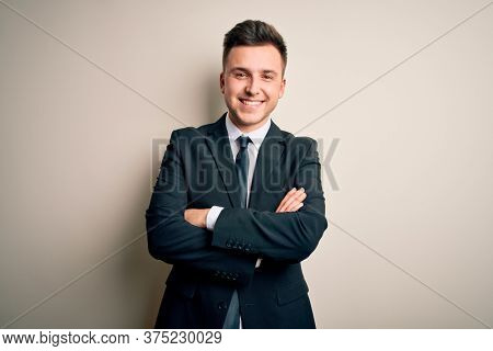 Young handsome business man wearing elegant suit and tie over isolated background happy face smiling with crossed arms looking at the camera. Positive person.