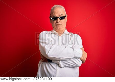 Middle age hoary man wearing funny sunglasses over isolated red background skeptic and nervous, disapproving expression on face with crossed arms. Negative person.