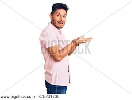 Handsome latin american young man wearing casual summer shirt pointing aside with hands open palms showing copy space, presenting advertisement smiling excited happy
