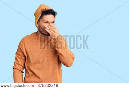 Handsome latin american young man wearing winter sweater and wool hat smelling something stinky and disgusting, intolerable smell, holding breath with fingers on nose. bad smell