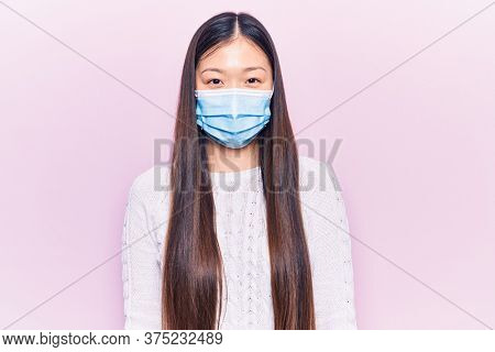 Young beautiful chinese woman wearing medical mask with a happy and cool smile on face. lucky person.
