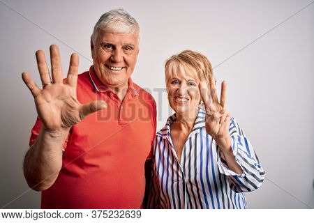 Senior beautiful couple standing together over isolated white background showing and pointing up with fingers number eight while smiling confident and happy.