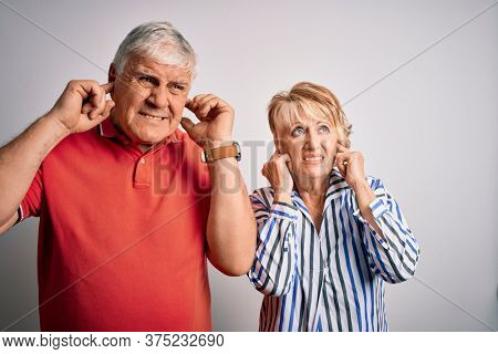 Senior beautiful couple standing together over isolated white background covering ears with fingers with annoyed expression for the noise of loud music. Deaf concept.