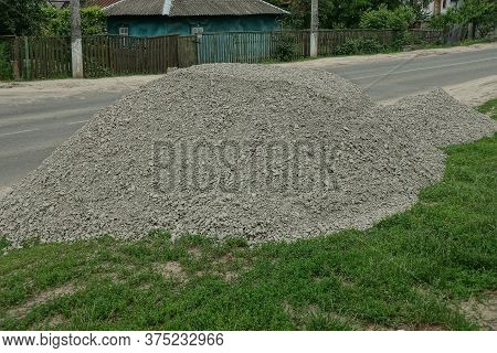 One Large Gray Pile Of Rubble From Small Stones On Green Grass On The Street By An Asphalt Road