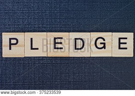 Text On Word Pledge From Gray Wooden Letters On A Black Background