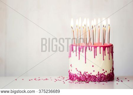 Birthday cake with pink drip icing and birthday candles with copy space to side