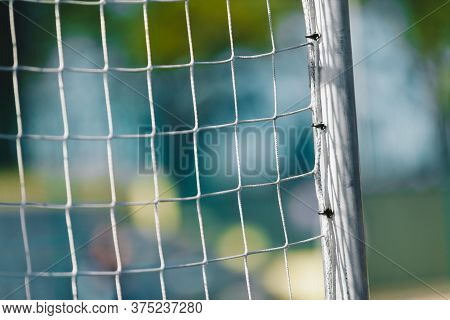 Soccer Football Goal With Net. Football Pitch Field With Stadium In The Background. Soccer Detail Cl