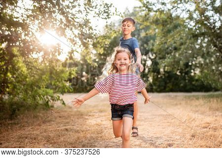 Happy Children Boy And Girl Frolic In The Park. The Older Brother Plays With His Sister In Nature In