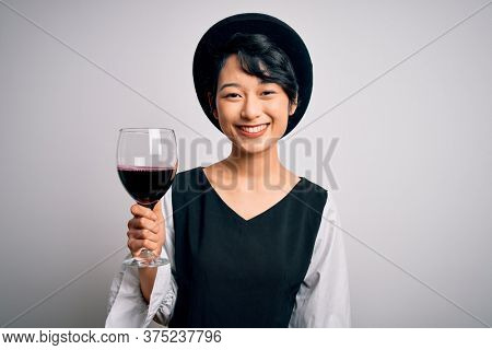 Young beautiful asian sommelier girl drinking glass of red wine over isolated white background with a happy face standing and smiling with a confident smile showing teeth