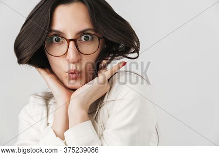 Photo of amusing businesswoman making fun and grimacing on camera isolated over white background