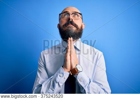Handsome business bald man with beard wearing elegant tie and glasses over blue background begging and praying with hands together with hope expression on face very emotional and worried. Begging.