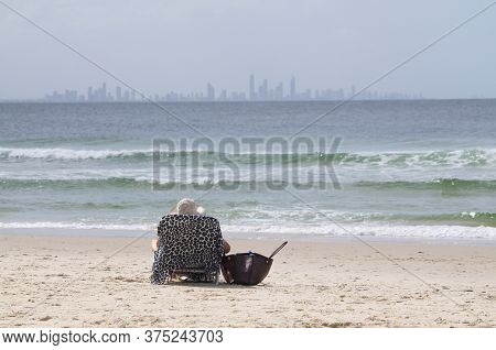 Rear View Of A Woman Sitting On A Deck Chair On The Beach Of Coolangatta With The City Skyline Of Su